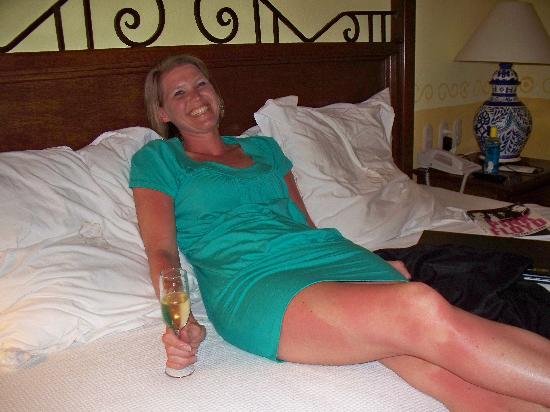 Occidental Cozumel: Wife enjoying complimentary bubbly on our king bed