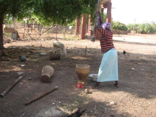 Bamako, Malí: This woman is grinding grain (corn, millet or peanuts) for the evening meal.