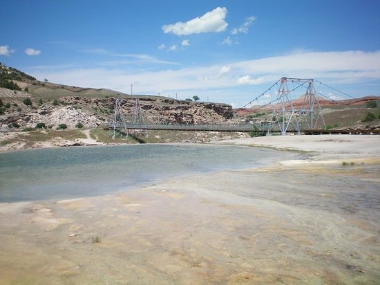 A hot sping in Thermopolis, Wyoming with a bridge in the background.