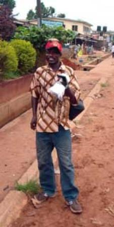 Benin City, Нигерия: The rat man! He has a mummified rat on his hat and in his hand. He sells rat poison and can prov