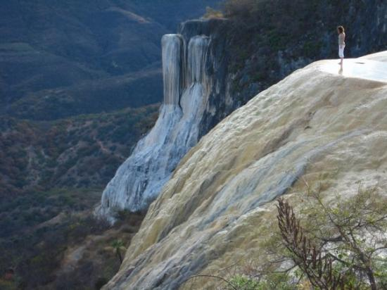 Oaxaca, Mexico: That's the petrified waterfalls.  Water rich in minerals bubbles out at the top of the ledge and