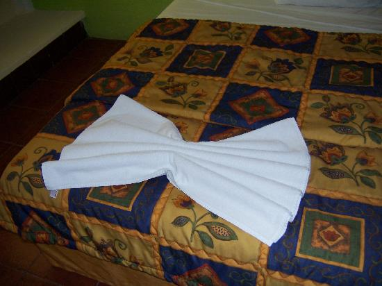 Hotel Plaza Cozumel: Bed, with an attempt of folding the towel into an animal (i think). Made me smile.