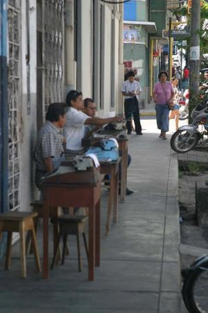 Iquitos, Peru: Men with manual typwriters waiting for someone who needs typing.  They sit with paper and carbon