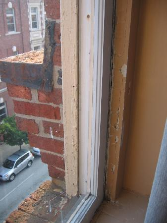 Midtown Inn: Room 118 window frame. Chpped, peeling, pitted.