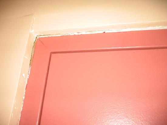 Midtown Inn: Room 118 door frame. Chipped, cracked, peeling.