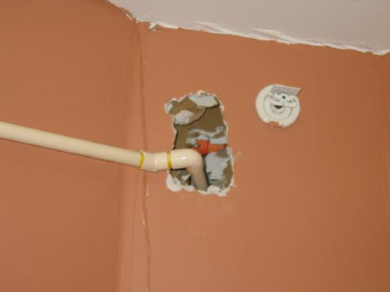 Midtown Inn: Hallway piping running out of gaping holes in wall.
