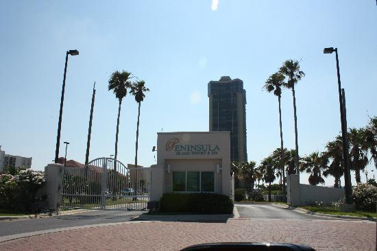 Peninsula Island Resort & Spa: Hotel entrance gate.   The tall building is not another propoerty. Peninsula is only 6 stories.