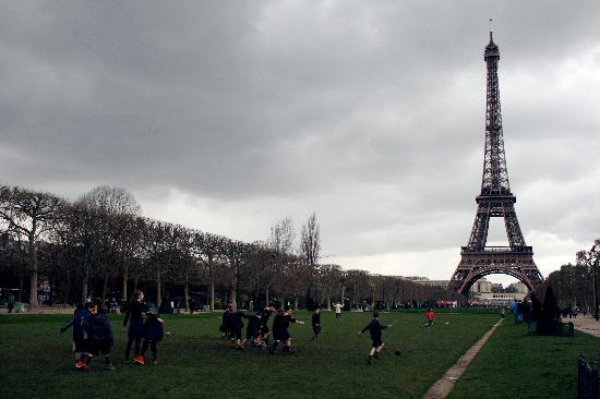 Parijs, Frankrijk: children playing soccer under the eiffel
