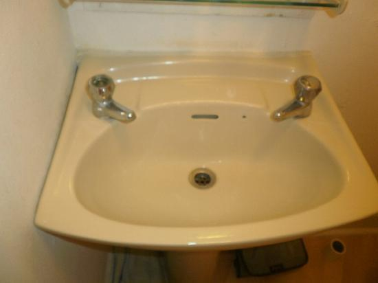 The Brighton Beach Hotel: Sink with no plug and part of hot tap missing