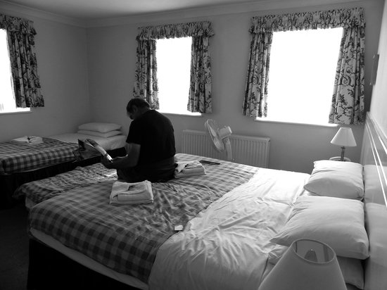 "Kingsland Hotel: Most of our ""quad"" room, all beds visible (and jetlagged father reading the paper)"