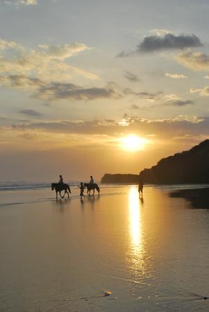 Alila Villas Soori: 2 guests on horseback on blacksand beach with beautiful sunset as backdrop