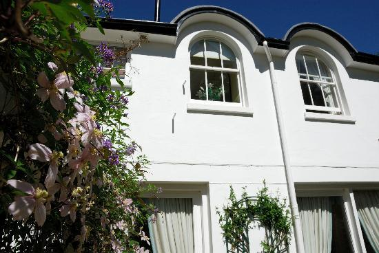 A & A Studley Cottage Bed and Breakfast : Two arched windows (twin bedded room) with flowers hanging from pergola