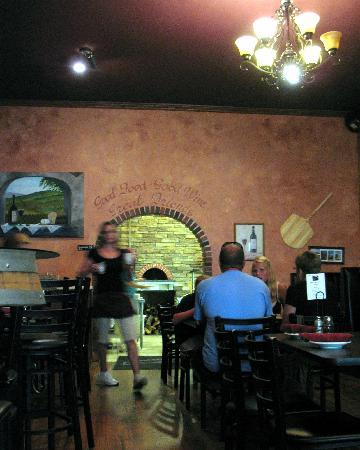 Interior of dining area showing the brick oven in the back
