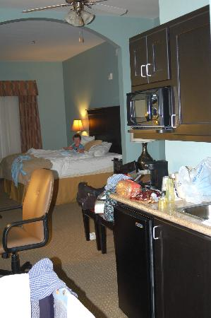 Kitchenette, ceiling fan & baby enjoying the king size bed in our room