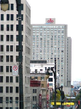 Hotels Gouverneur Montreal: Hotel tower with a view down Ste. Catherine Street--building with logo on top.