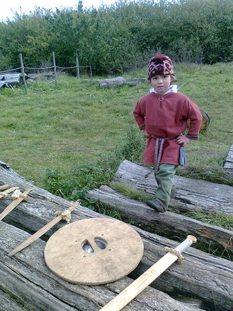 West Stow Country Park and Anglo-Saxon Village: A young villager explaining the use of the axe, sheild and swords.