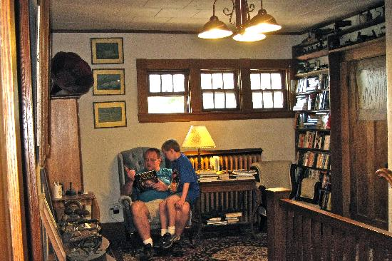 Caribou, ME: My son reading one of the books found in the upstairs hall to my grandson.