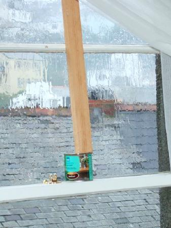 St. James Apartments: Sash window propped up with wood & varnish pot!!