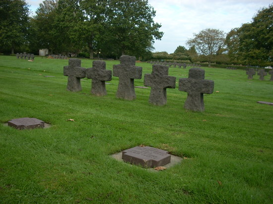 La Cambe, Prancis: Black stone crosses alternate with markers that are flush with the grass.