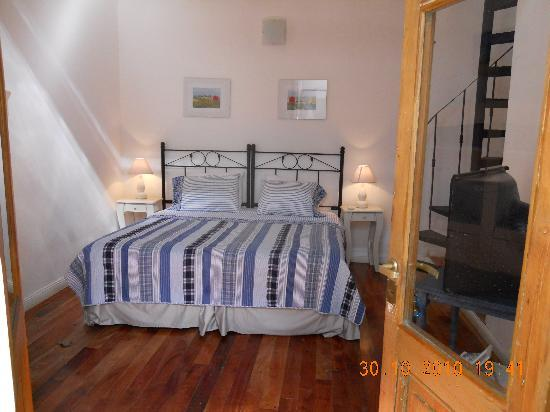 Simple and Charming Inn: downstairs bedroom showing tv & spiral stairs to upstairs bedroom