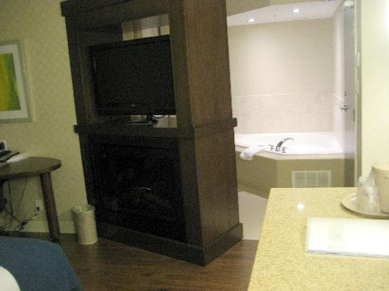 Holiday Inn Express Toronto - Markham: Jetted tub in the back, big-screen TV on top, electrick fireplace on bottom. Bed to my left.