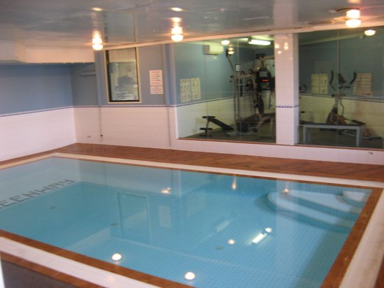 swimming pool with gym on the other side of glass wall ...