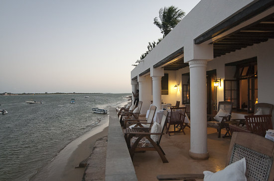 Peponi Hotel: Watching the sun com down as the waves splash softly against the wall below