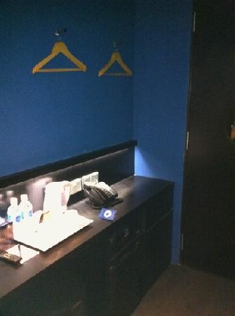 โรงแรมพอร์ซเลน: wall serves as cupboard and mites on e small table. photo taken from the bed.