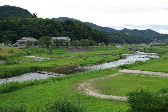 Gassan Toda castle: 飯梨川に架かる新宮橋の上から望む「道の駅(広瀬絣センター)」(左側)と「歴史資料館」(右側)です。広瀬絣センターの背後にあるのが月山です。