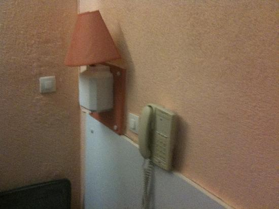 Hotel Montmartrois : Basic lamp and telephone above beds