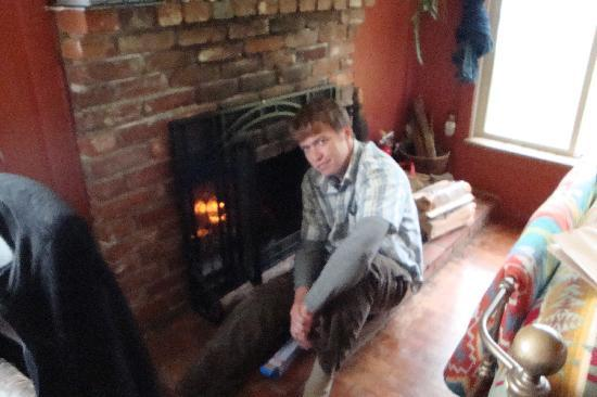 Ocean Haven: my fella in front of the fireplace on a former trip
