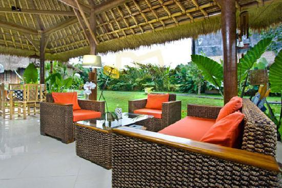Villa Kunang Kunang: A shady restaurant pavilion surrounded by manicured lawn, swaying palms and a vegetable garden c