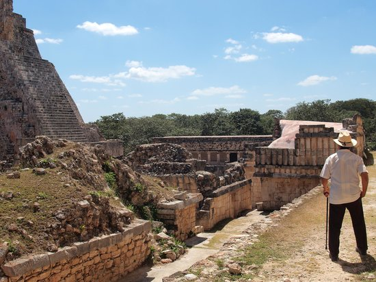 Uxmal Tapınakları: Older Mexican man looking out at the Pyramid of the Magician - dressed in modern Yucatan garb