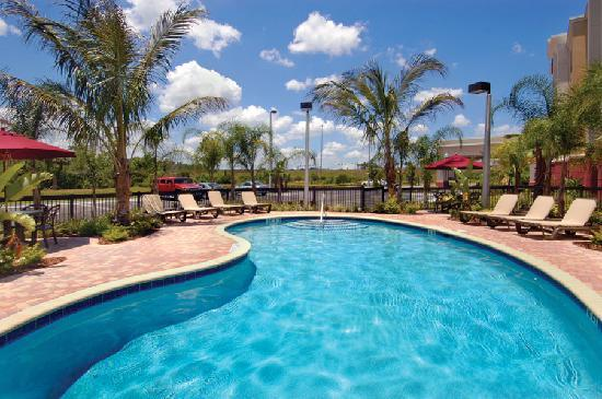 Hampton Inn & Suites Tampa-Wesley Chapel: Tropical landscaping surrounds the crystal clear water of the outdoor pool.