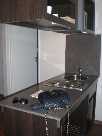 Fertilia Downtown Apartamentos: balcão com fogão, microondas, pia, frigobar, louças.