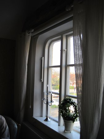 "Annas Hotell: One of the windows in the balcony room, showing a ""candle"" lamp and live plant. Roll-down shades"