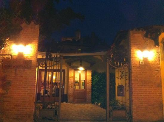 Trattoria la Casetta: L'ingresso della Casetta alla sera. Sullo sfondo uno dei tre castelli di Brisighella.