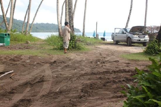 For Rest Boutique House: The muddy path to the beach, and the pickup truck from whose stereo the locals were playing loud