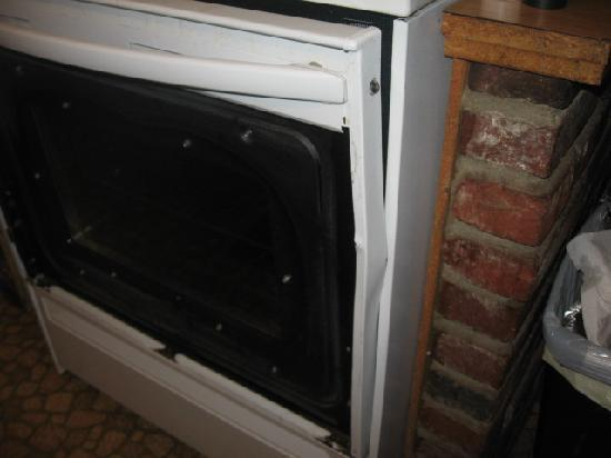 Paulina Lake Lodge: Kitchen stove with missing part of front door and the dent to keep the door from latching