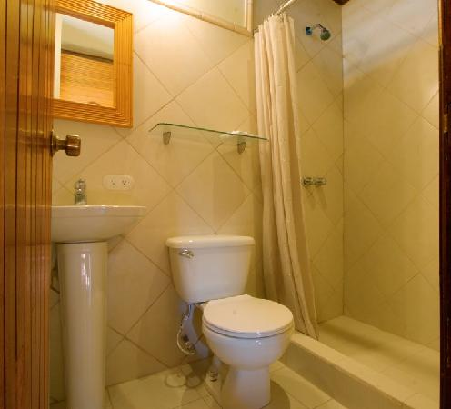 Villas Oasis: The Hideaway bathroom all covered in white tile and wooden features