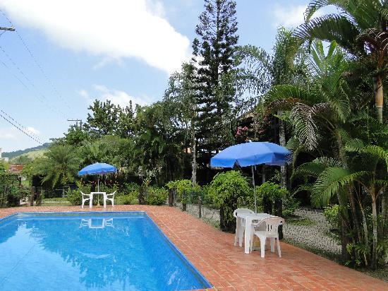 Pousada Acqua Flats Ubatuba: Piscina em meio a jardim tropical