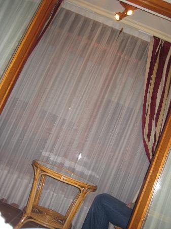 El Capitán Hotel: Terraza cerrada con mesa y sillas de mimbre