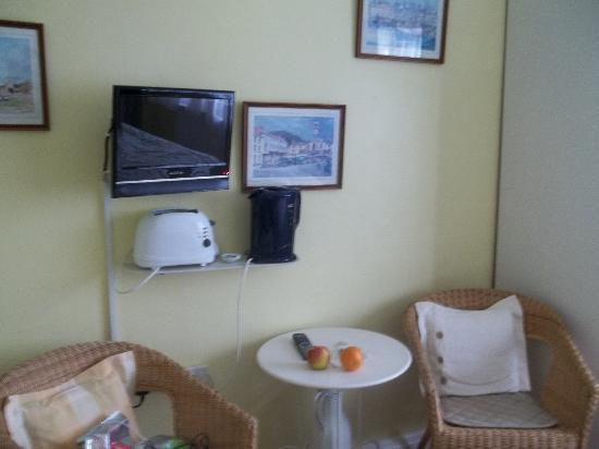 Ross House Guest House: Seating area with little table to eat at. TV on the wall with toaster and hot water kettle on sh