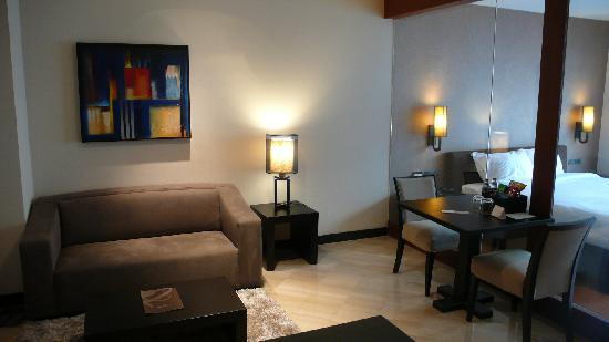 Pietra Bangkok Hotel : living & dining area separated from bedroom by glass wall in the suite