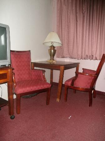 Magnuson Inn: Broken table in the corner of the room and dirty carpet