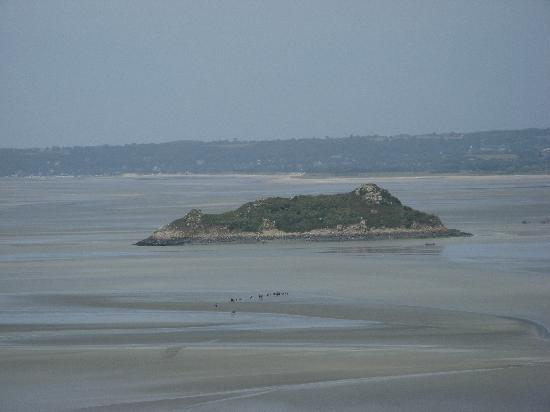 Mont-Saint-Michel, France: Look down from the heights of MontSt-Michel at a tour group walking out on the ocean at low tide