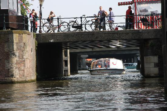 Amsterdam, Holandia: Canal boat going under stone bridge