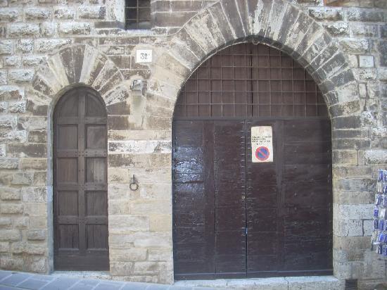 """Gubbio, İtalya: il portone con a fianco la tipica """"porta del morto"""", che tradizionalmente si apriva solo in occa"""