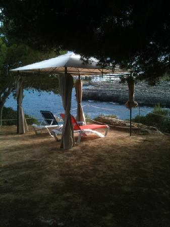 Hotel JS Cape Colom : detalle terraza, tumbonas bajo pérgola, jardín frente al mar