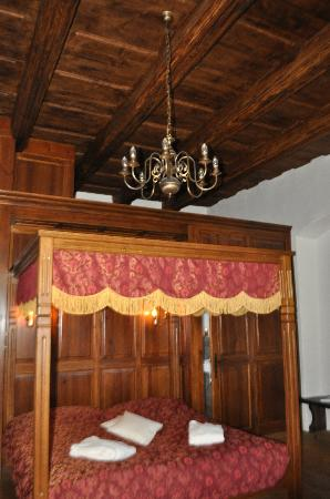 Zamek Zabreh: The bed with the wood-beamed ceilings and wood walls.